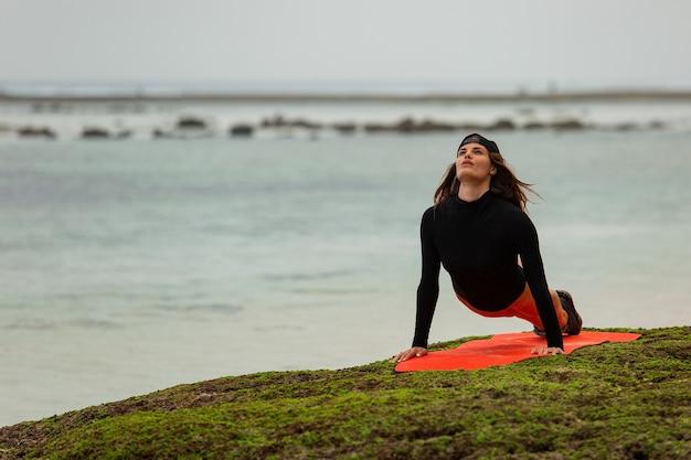 La bella donna dai capelli castani va per lo sport sulla spiaggia