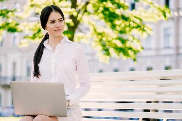 Bella bruna imprenditrice in camicia bianca, lavoro a distanza all'aperto sul suo computer portatile all'aperto,