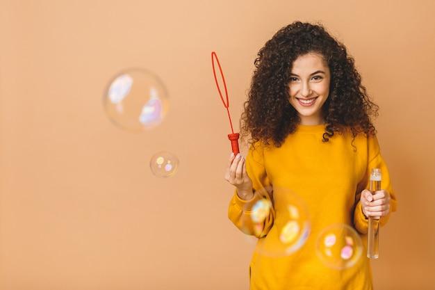 La bella ragazza riccia castana dello studente indossa le bolle di sapone di fabbricazione casuali isolate su fondo beige.