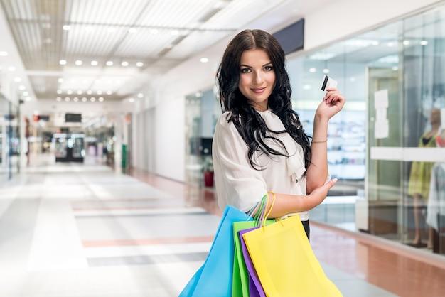 Bella bruna facendo shopping con carta di credito