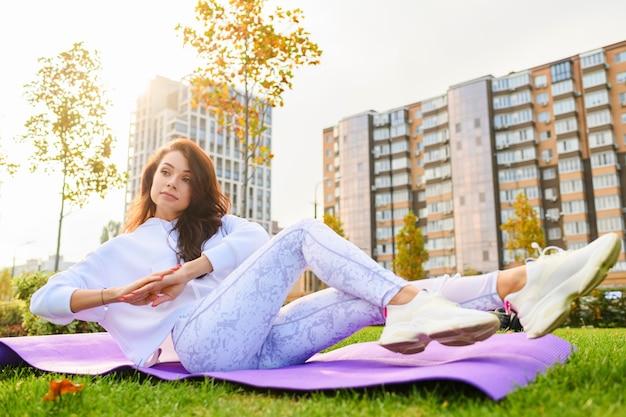 Bella donna bruna sdraiata al tappetino sportivo in abbigliamento sportivo bianco, facendo addominali, fitness, esercizi di stretching yoga con edifici della città moderna dietro