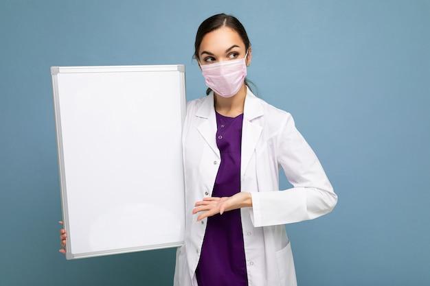 Bella infermiera femminile castana in maschera protettiva e camice medico bianco che tiene un vuoto
