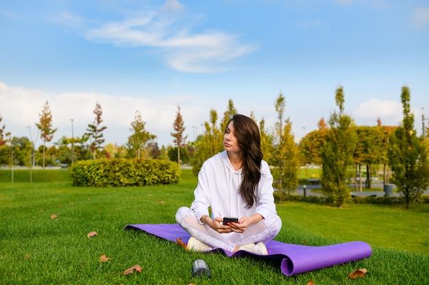 La bella femmina castana si siede sulla stuoia porpora al parco verde della città, tiene il telefono e si rilassa dopo l'allenamento, ginnastica