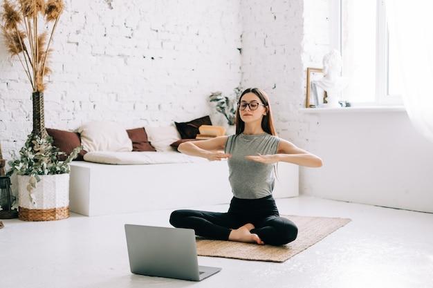 La bella donna castana di forma fisica fa gli esercizi di stretching