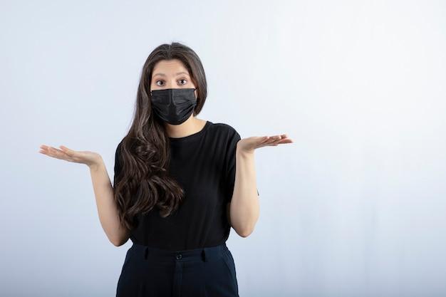 Bella ragazza castana in maschera medica nera in piedi e in posa contro il muro bianco.