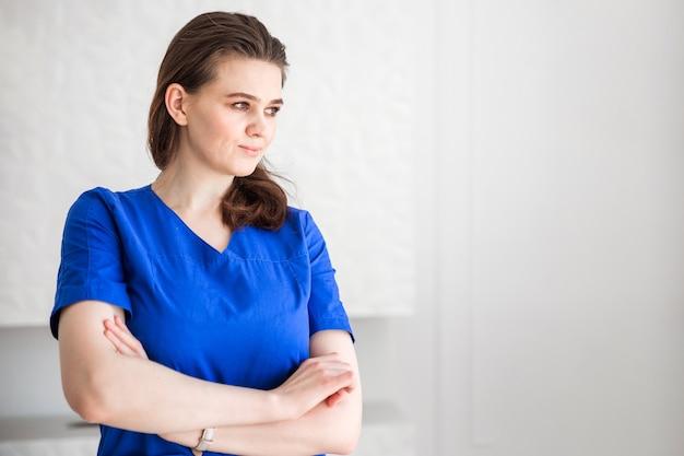 Il medico della bella ragazza castana in un vestito blu osserva al lato.