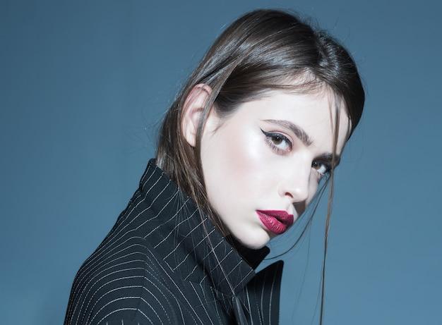 Primo piano del viso di bella ragazza castana in giacca nera o cappotto isolato su capispalla alla moda grigio freddo inverno o caduta