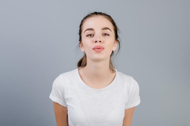 Bella ragazza castana che flirta soffiando un bacio isolato sopra grey