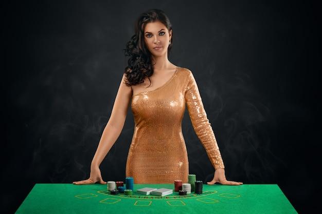 Una bella ragazza castana con un vestito da croupier lucido dorato si trova davanti a un tavolo da gioco