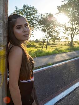 Bella ragazza castana che posa sulle foto in natura nel tramonto.