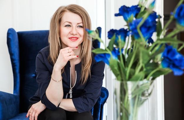 Bella ragazza castana si siede su una poltrona di velluto blu e guarda un mazzo di fiori blu.