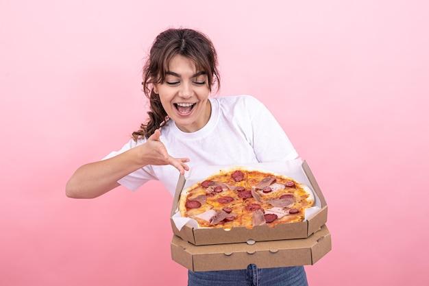 Bella ragazza bruna sorridente, con in mano una scatola di pizza per la consegna, sfondo rosa, copia spazio.
