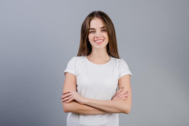 Bello sorridere della ragazza del brunette isolato sopra la parete grigia