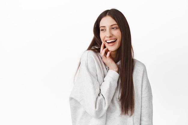 Bella ragazza bruna che si tocca il viso, ride e guarda da parte lo spazio della copia del logo, guardando il lato sinistro con felice espressione felice, in piedi sul muro bianco