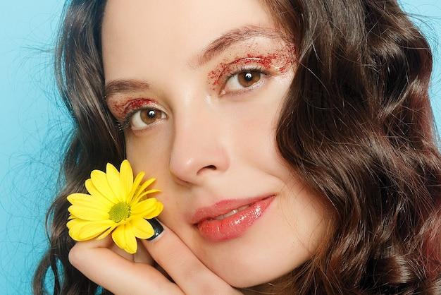 Bella ragazza bruna con occhi verdi make up e pelle fresca in posa su sfondo blu con fiore, concetto di cura della pelle, spa di bellezza, prodotto bio. orizzontale
