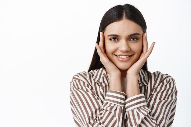 Bella ragazza bruna con un sorriso felice, toccando il viso con la punta delle dita vicino agli occhi, usando cosmetici per la cura della pelle per un risultato facciale nutrito, muro bianco