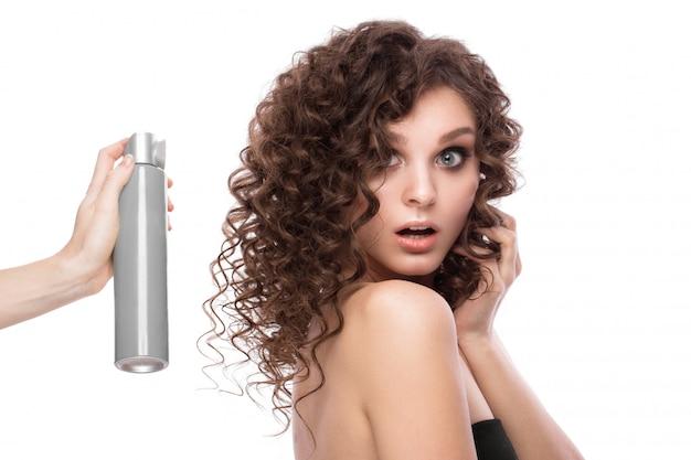 Bella ragazza bruna con i capelli perfettamente ricci con flacone spray e trucco classico. volto di bellezza.