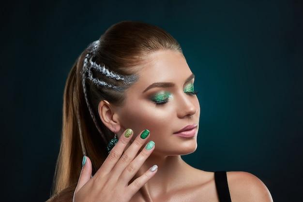 Bella ragazza castana con l'acconciatura alla moda con elementi di trucco brillante argento e verde in posa. donna che tocca il viso a mano, mostrando una perfetta manicure. concetto di bellezza.