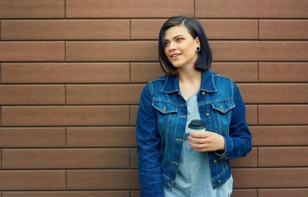 Bella ragazza castana con tunnel nelle orecchie in una giacca di jeans blu con una tazza di caffè in piedi davanti al muro di mattoni.