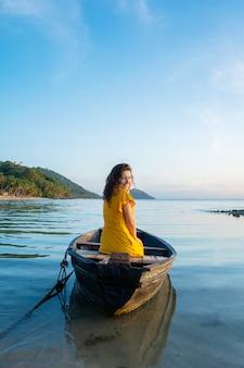 La bella ragazza castana in un vestito giallo si siede in una vecchia barca di legno che trascura un'isola tropicale abbandonata. romanticismo in mare