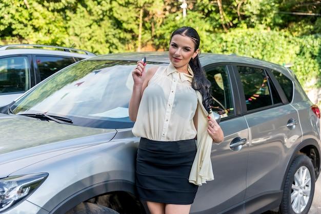 Bella bruna che tiene la chiave dalla nuova automobile