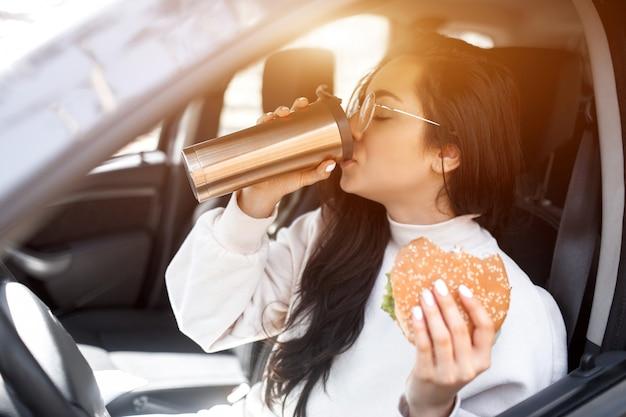 Bellissima modella bruna pranza in macchina. la donna mangia un hamburger e beve caffè o tè da un thermos. food on the road concept.