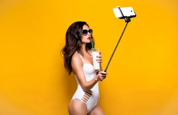 Bello modello castana in occhiali da sole e presa bianca di monokini