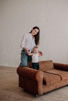 La bella mamma bruna gioca con la sua piccola figlia su un divano marrone
