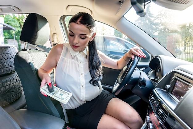Bella bruna che offre banconote in dollari e chiave della macchina