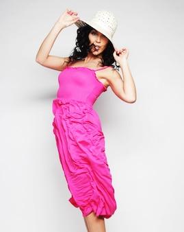 Bella bruna in abito rosa con cappello che salta