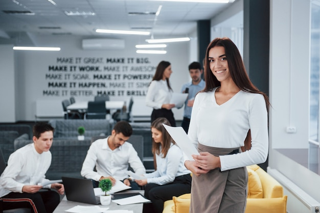 Bella bruna il ritratto della ragazza sta nell'ufficio con gli impiegati a fondo