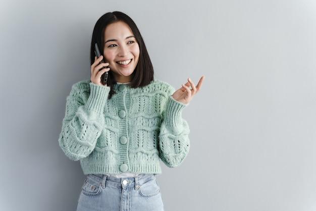 Bella bruna parlando al telefono isolato su uno sfondo grigio