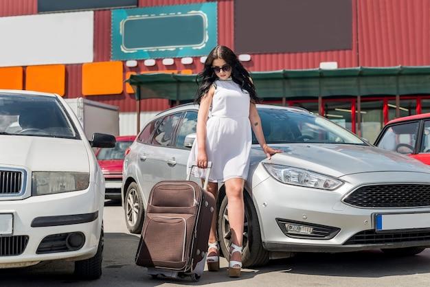 Bella bruna che viaggia con la valigia in macchina