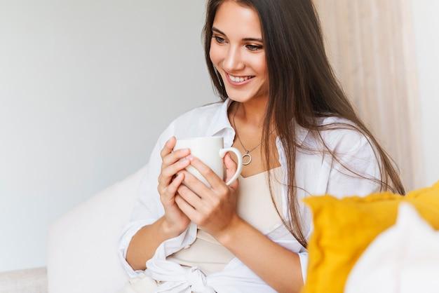 Bella bruna in camicia bianca si siede sul divano bianco, tenendo la tazza bianca con caffè caldo in mano.