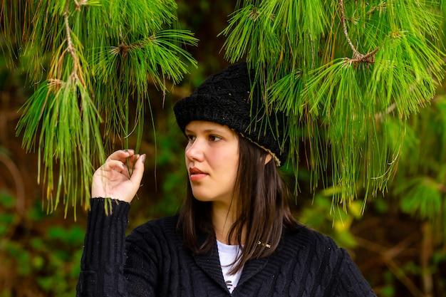 Bella donna castana in mezzo ai rami e alle foglie dell'abetaia un giorno di inverno