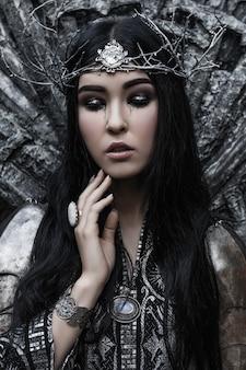 Bella donna castana in un vestito e un'armatura neri e argento