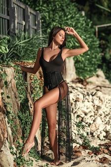 Bella donna bruna in costume da bagno nero e mantello in posa sulla spiaggia