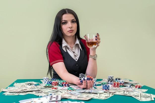Bella donna bruna al casinò con un bicchiere di bevanda