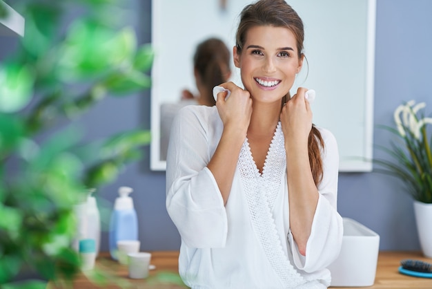 Bella donna bruna che pulisce il viso in bagno