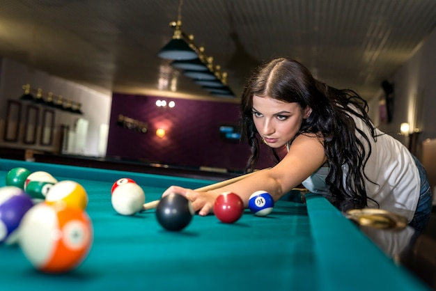 Bella donna castana concentrata sul gioco del biliardo