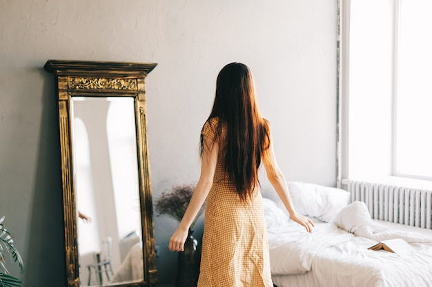 Bella donna castana in vestito in piedi vicino al grande specchio in camera da letto e guardando se stesso, montaggio nuovo vestito.