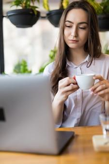 Bella donna castana che beve caffè e che utilizza computer portatile nella caffetteria