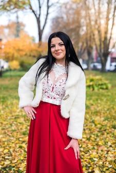 Bella donna castana in integrale che posa in vestito elegante