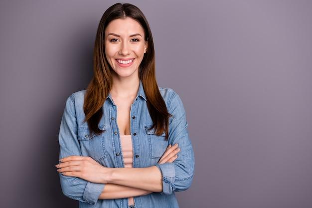 Bella donna bruna in camicia di jeans in posa contro il muro viola
