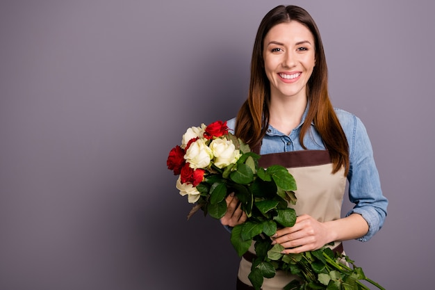 Bella donna castana in camicia di jeans in posa con bouquet contro il muro viola