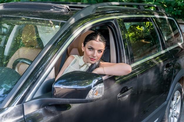 Bella donna castana che guarda attraverso il finestrino della macchina
