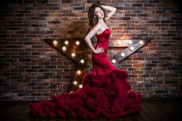 Modello di bella donna castana in vestito rosso di lusso con il trucco