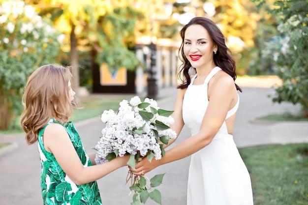 Bella donna bruna mamma con sua figlia che cammina nel parco o nel giardino primaverile tra i lillà in fiore