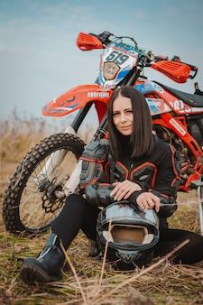 Bella donna castana in attrezzatura del motociclo.