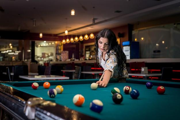 Bella donna castana che gioca biliardo nel pub